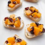 Looking for a perfect fall appetizer? Cranberry Goat Cheese and Butternut Squash Toast is perfect for fall parties, pre-holiday dinner snacks, or just as an appetizer before dinner. This butternut squash toast assembly combines all of the perfect fall flavors, with sweetness from cranberries and butternut squash met with the tanginess and softness of goat cheese spread on a toasted baguette.?