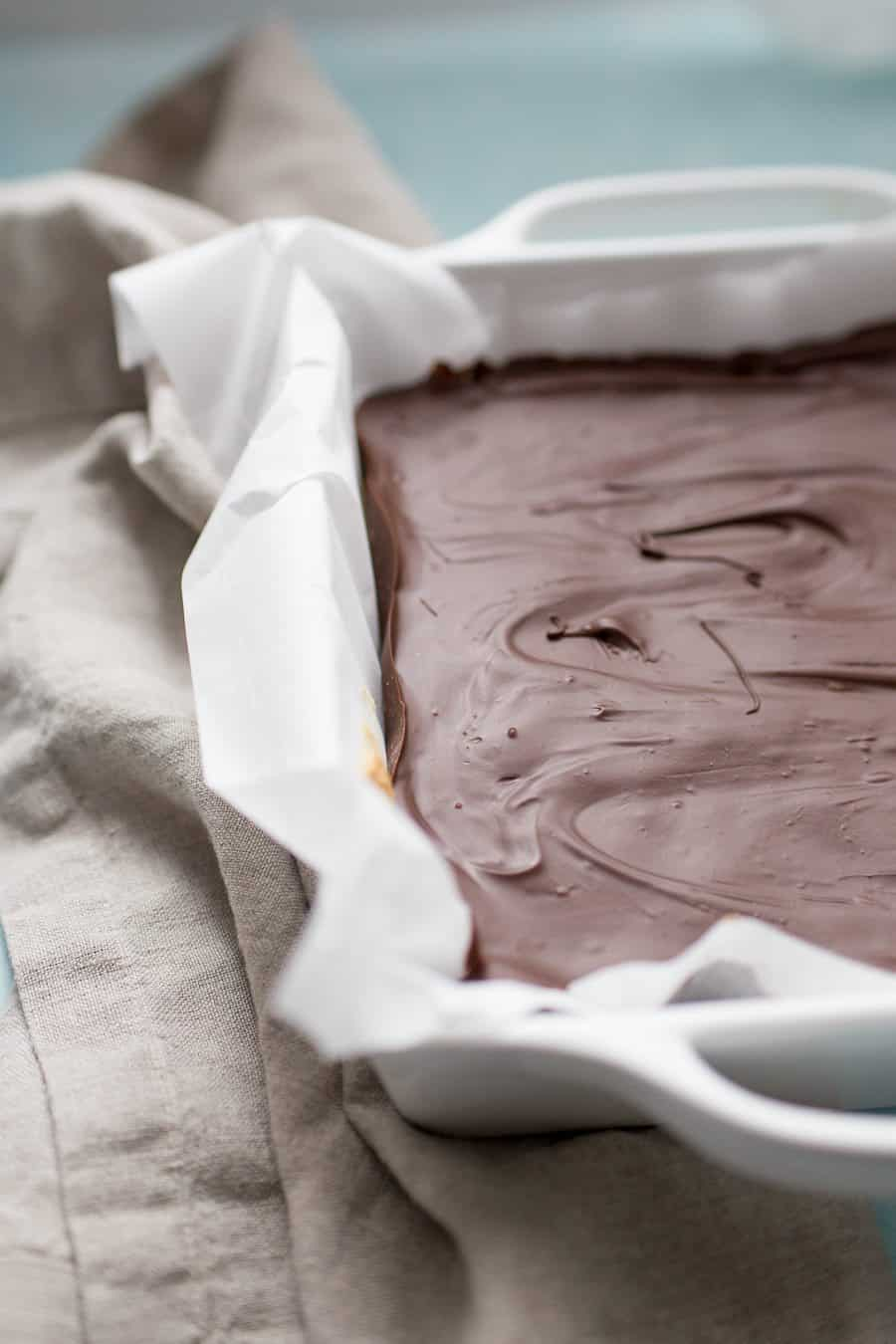 Chocolate bars in a white square baking dish lined with parchment paper, on top of a beige towel.