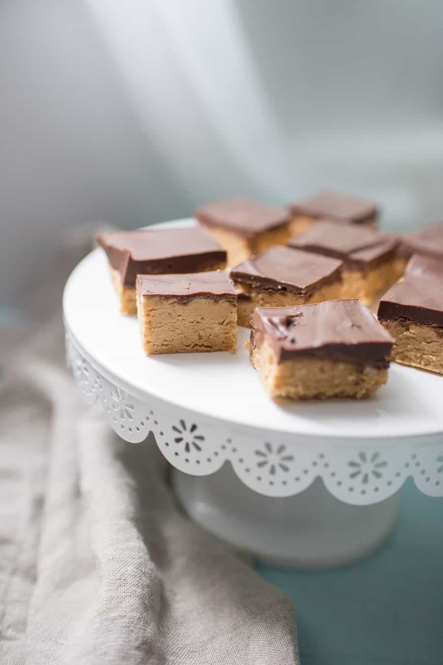 White cake stand with peanut butter and chocolate squares on top.