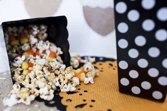 Candy Corn Caramel Popcorn spilling out of a popcorn container onto a black doily