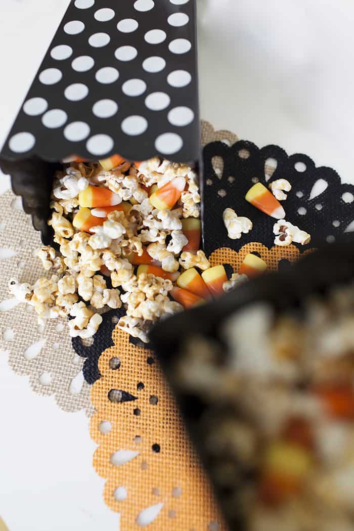 top view of Candy Corn Caramel Popcorn spilling out of a black popcorn basket