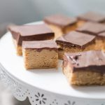 No Bake Peanut Butter Chocolate Bars are incredibly easy to make ahead of time and serve for any event! These indulgent, creamy treats are sure to disappear quickly and you'll be wishing you had more! These no bake dessert bars are made with just a handful of ingredients, but make no mistake they are not lacking in any sort of delicious flavor. A crunchy peanut butter and graham cracker crust is topped with smooth chocolate and creates the perfect peanut butter and chocolate combination that everyone will drool over.?