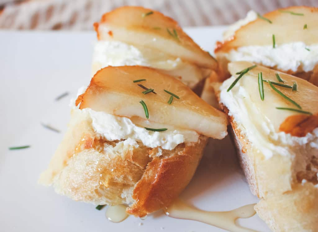 Sliced baguette with goat cheese on top, topped with a sliced pear and sprinkled with rosemary.