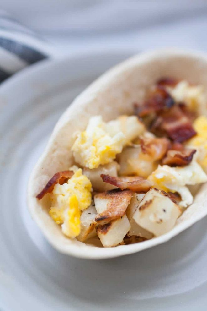 These bacon breakfast scramble bowls are the perfect way to start the weekend! Customize these bowls with your favorite breakfast protein, veggies, and toppings like cheese, green chile or salsa. Or keep them simple with potatoes, eggs and bacon! Either way, these breakfast bowls are sure to be a hit with your family.