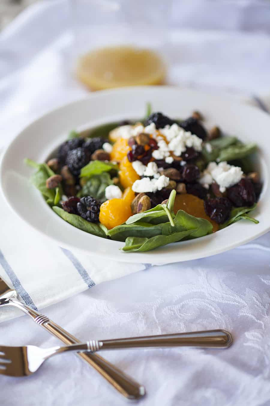 This citrus berry spinach salad is loaded with ingredients like pistachios, cranberries, goat cheese, oranges and blackberries and it's perfect for a summer salad!