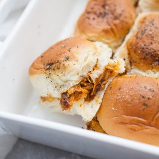 White baking pan with chicken sliders.