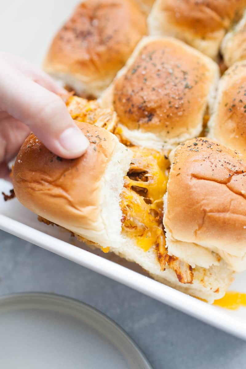 Puling apart chicken sliders with cheese in a pan.