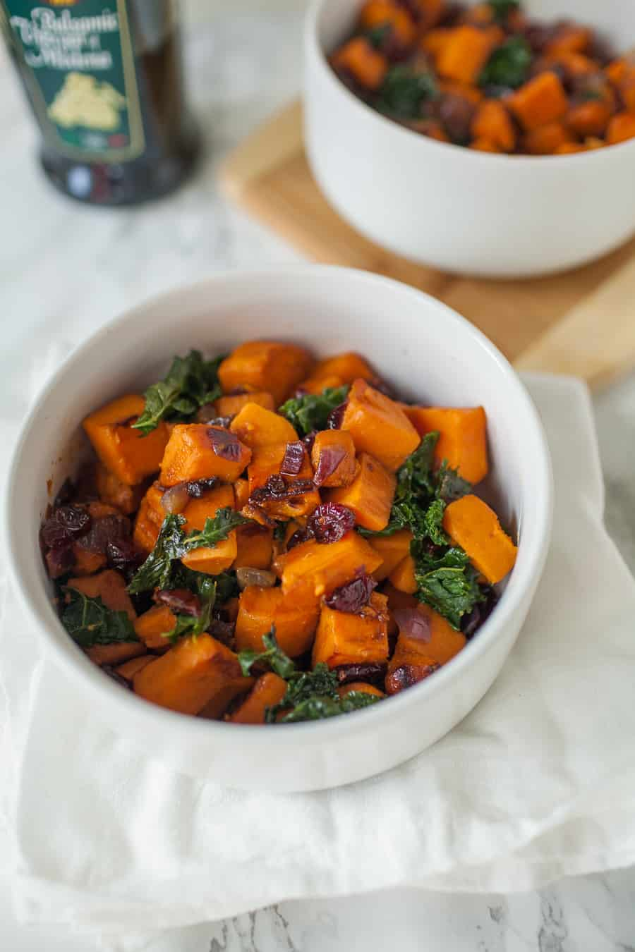 In need of a quick but delicious side dish for dinner? This sweet potato and kale saut? is perfectly delicious and easy to make. The sweet potatoes are the star of this show, but the red onions, cranberries, kale and a splash of balsamic vinegar make this dish robust in flavor! easy side dish | side dish ideas | sweet potatoes | kale | red onions | onions | cranberries | balsamic vinegar