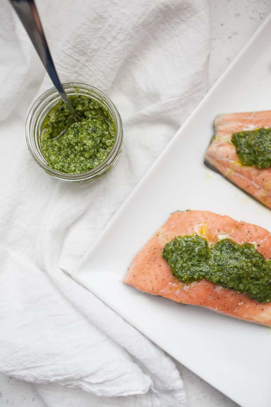 If you're looking for a quick dinner that won't lack in flavor, this kale arugula pesto salmon is it. Made with homemade pesto and baked for twenty minutes, it's a quick and flavorful dinner recipe. Baking salmon in the oven is a quick way to make it and easy for someone who might not make salmon often! salmon pesto | pesto salmon | homemade pesto | baked salmon | salmon dinner | how to bake salmon | baked salmon dinner