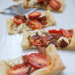 This?Tomato Bacon Goat Cheese Puff Pastry Appetizer?is the perfect pre-dinner snack when you're hosting friends and family! It's so quick to throw together and enjoy while dinner finishes cooking. A simple frozen puff pastry topped with ?crispy bacon pieces, dollops of goat cheese and sliced grape tomatoes makes a quick appetizer that everyone will enjoy!?