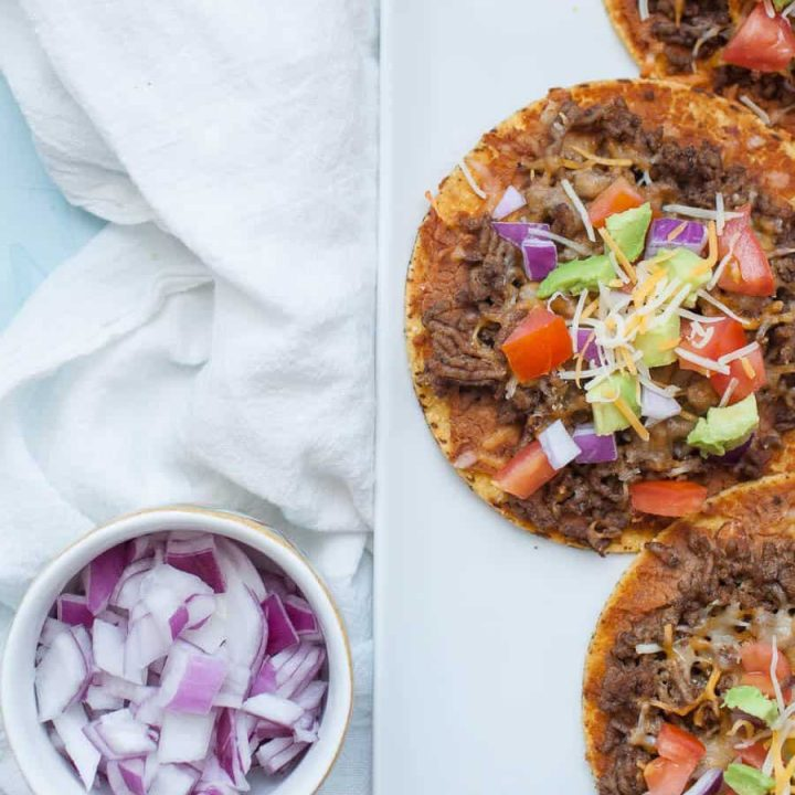 Easy ground beef tostadas are the perfect dinner for busy weeknights! They're quick to make and can be customized a ton of ways to be your perfect flavor combination! Start with a flat, crunchy corn tortilla and add your toppings like beans, ground beef, tomatoes, avocado and cheese for a flavorful, quick dinner.?