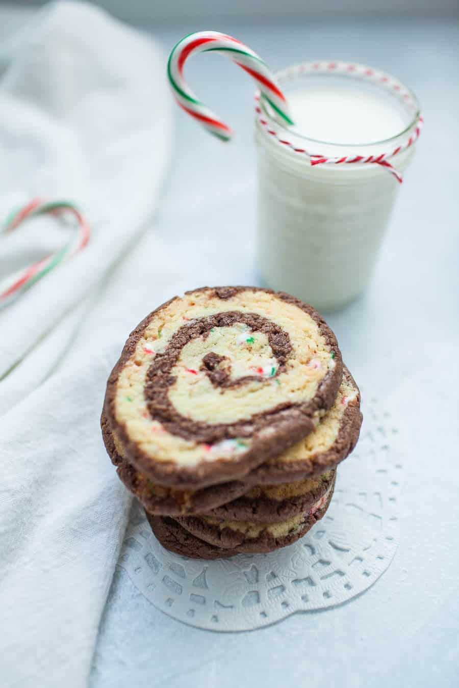 Chocolate Peppermint Pinwheel Cookies are the perfect cookie to share during the holidays! Two sheets of cookie dough, one that is smooth and chocolatey and one that is infused with peppermint and candy cane peppermint pieces, are rolled together to create these beautiful and festive pinwheel cookie slices. If you dream about the combination of peppermint and chocolate together during the holidays, these chocolate peppermint pinwheel cookies will be your new favorite Christmas cookie!