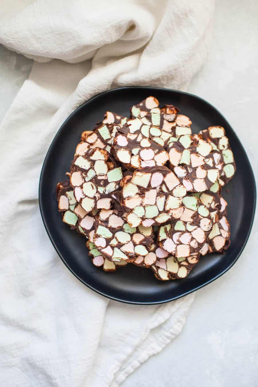 Dark gray stone plate with one inch thick stained glass window cookies, bright colored mini marshmallows and covered in chocolate.