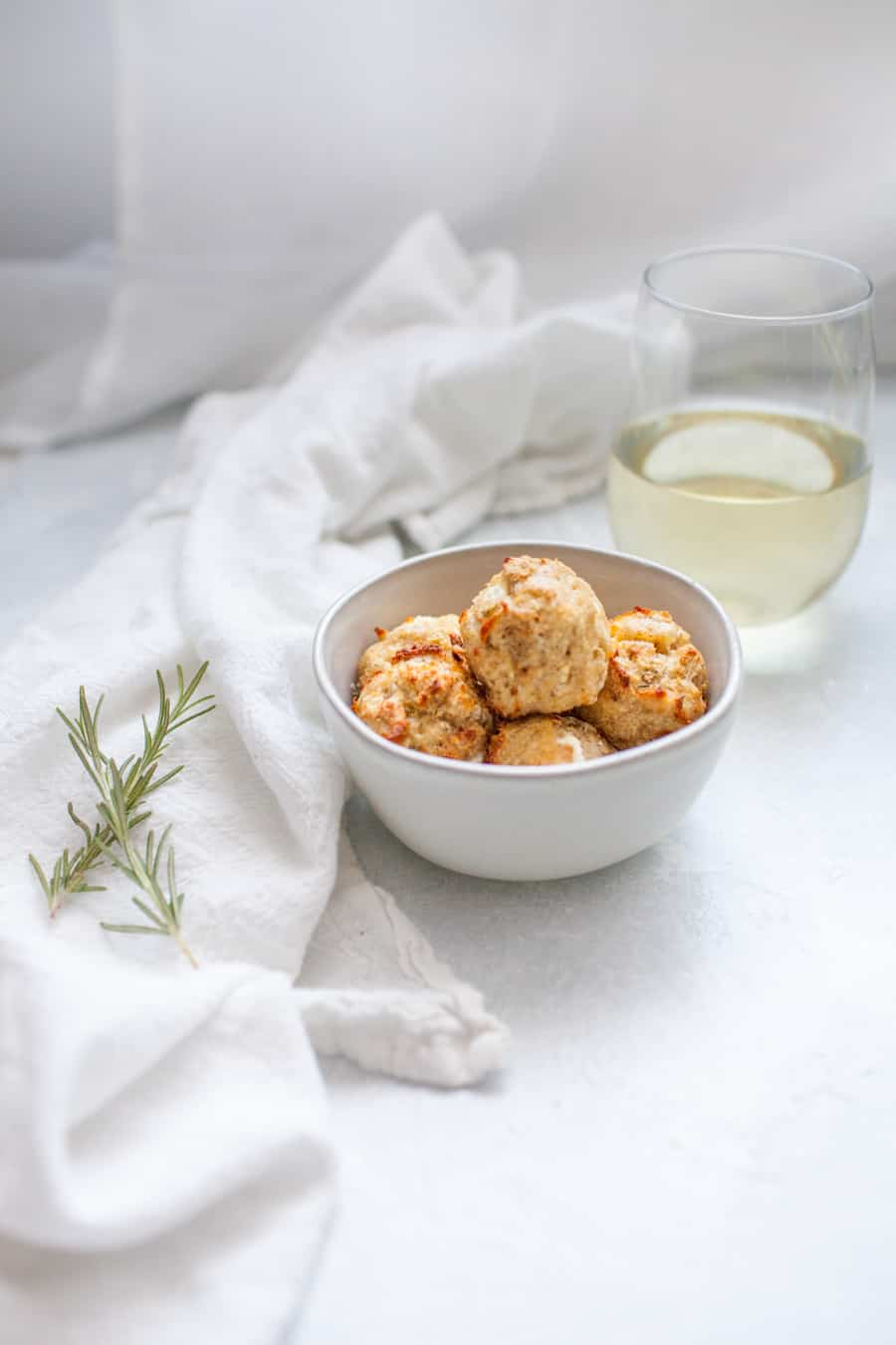Goat Cheese Rosemary Baked Chicken Meatballs are a perfect game day appetizer! These meatballs are made with ground chicken, fresh rosemary and creamy goat cheese and come together in under 30 minutes. They can also be the perfect protein for dinner, served over a salad, rice or pasta. Enjoy these baked chicken meatballs while sipping on a glass of Trivento Wine!