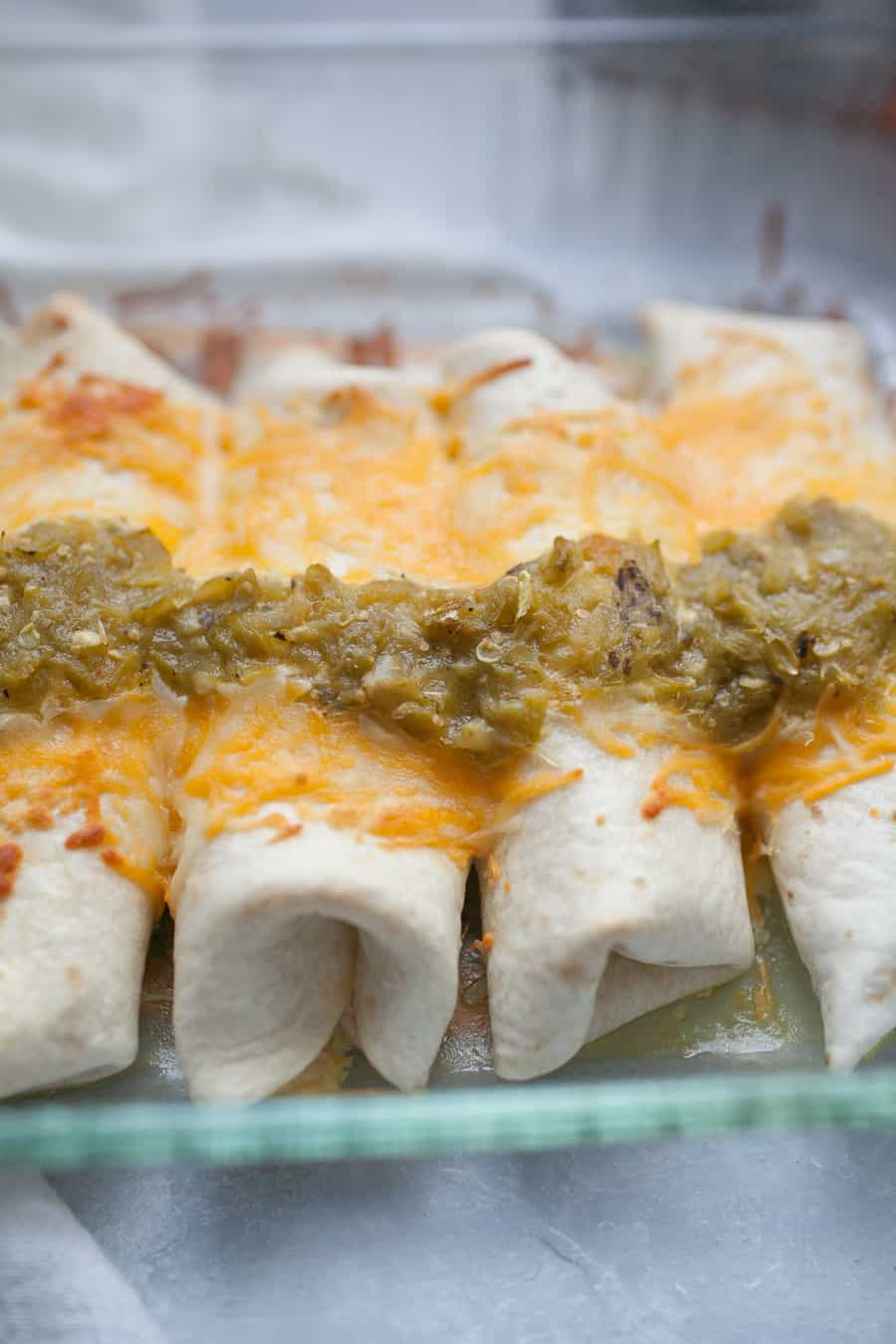 Sour Cream Chicken Enchiladas are the perfect weeknight dinner that will gather your family around the table. These enchiladas are made with flour tortillas, instead of traditionally used corn tortillas, and are stuffed with shredded chicken mixed with cream of chicken soup, sour cream, and cheese. The whole dish is topped with cheese and spicy green chile sauce! It's packed with flavor and the perfect dish for your family!?