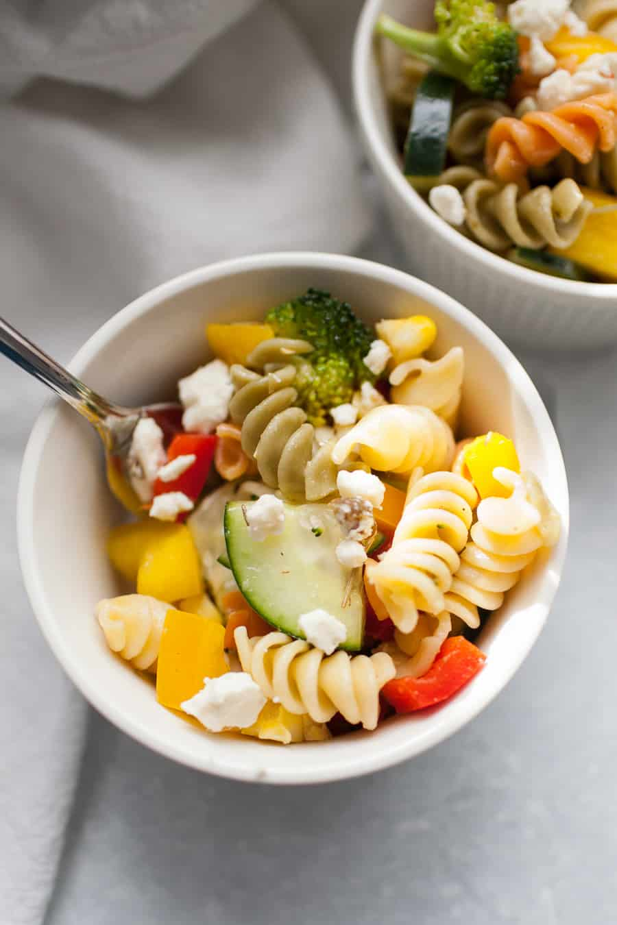Veggie packed pasta salad is a perfect side dish for any occasion. It's great for the warmer weather for potlucks outside and perfect for brightening the colder months, too! The pasta salad is made with a mayo-free dressing and packed with vegetables like cucumbers, bell peppers, tomatoes, corn and topped with feta cheese.