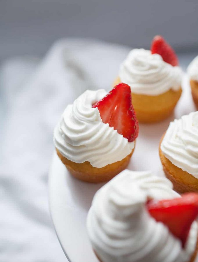 Strawberry Shortcake Cupcakes are the perfect dessert for any occasion. These cupcakes are light and fluffy and bring the experience of eating strawberry shortcake into a cupcake! Spruce up a boxed cake mix with a few add ins and your own homemade whipped cream icing that tastes just like the real thing. Top with a slice of fresh strawberry and you're ready to share these cupcakes over a cup of coffee with friends!?