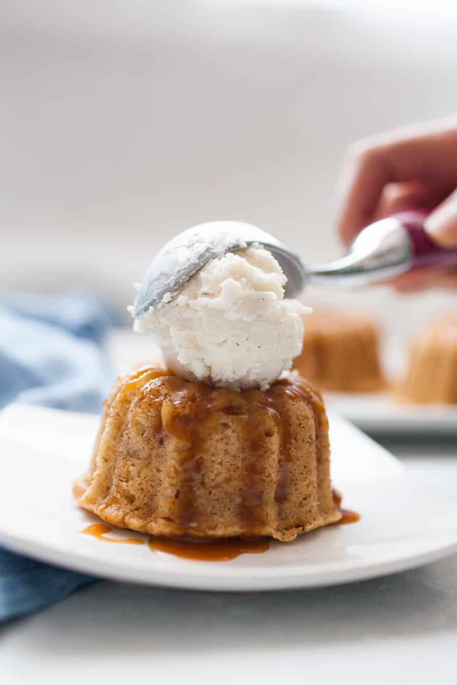 Scooping vanilla bean ice cream onto a mini spiced bundt cake sitting on a white square plate.
