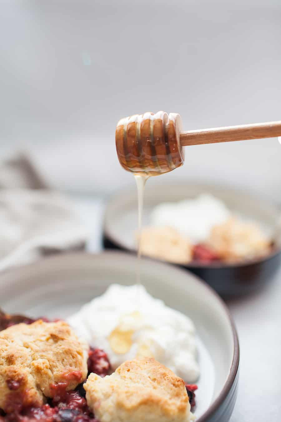 Honey pouring from a wooden honey dipper onto a shallow black bowl of triple berry cobbler with yogurt.