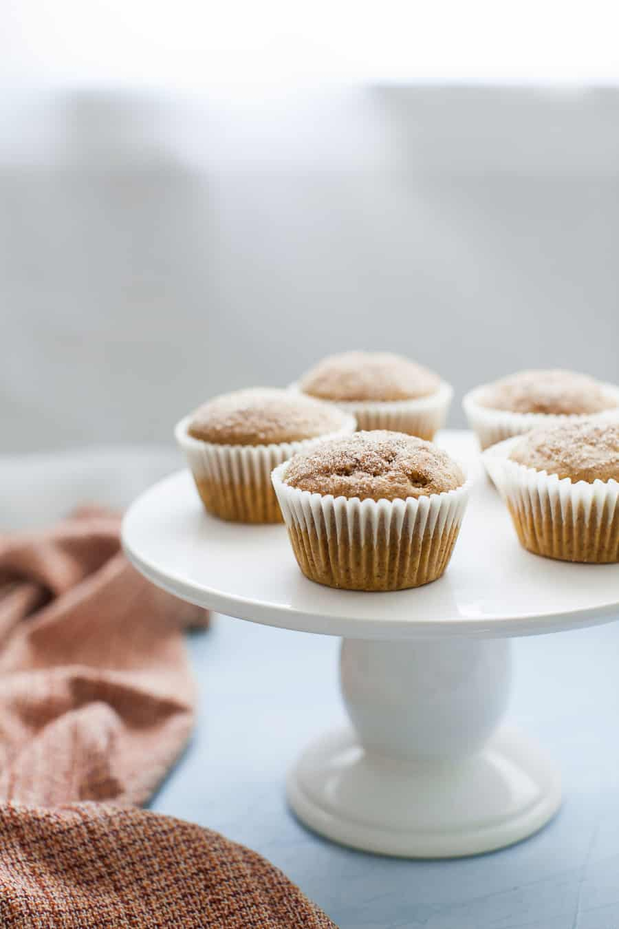 A batch of pumpkin muffins, wrapped in cupcake liners, sitting on top of a white porcelain cake stand.