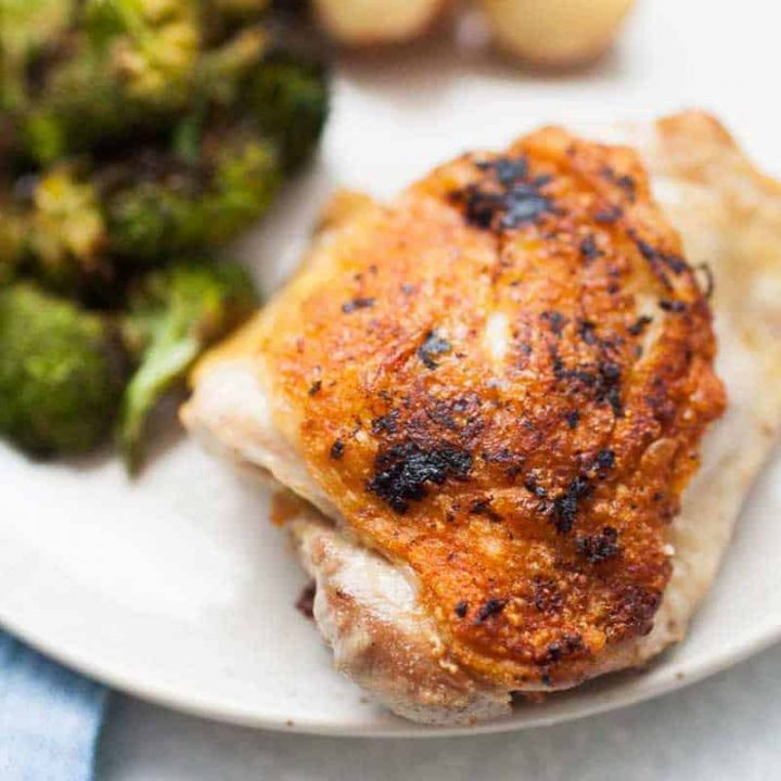 Close up of crispy chicken thigh with lemon pepper seasoning plated with broccoli.