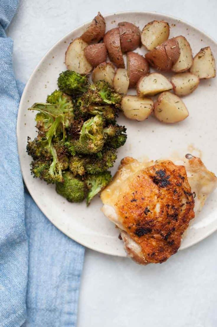 Close up of crispy chicken thigh with lemon pepper seasoning plated with broccoli and potatoes.