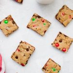 Christmas M&M Cookie Bar squares set on a tabletop with white milk glasses.