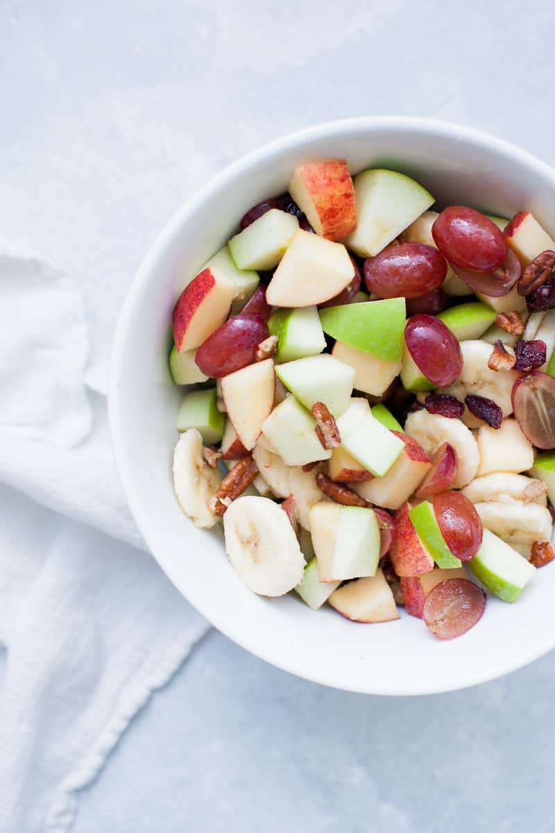 White bowl with red and green apples, pecans, grapes, bananas, and cranberries.