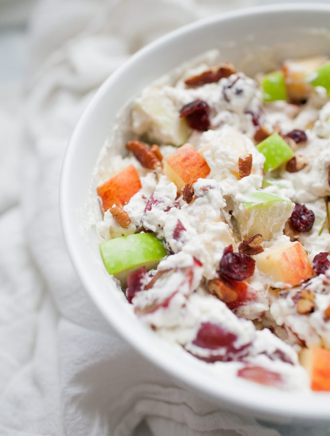 White bowl with creamy whipped cream topped fruit salad with red and green apples, grapes, bananas, cranberries and pecans.