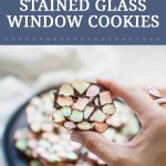 Pinterest image for stained glass window cookies. A female hand holding a cookie with colored marshmallows and chocolate.