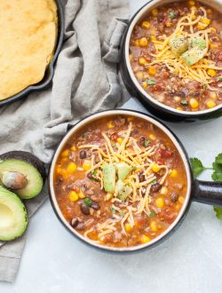Black soup bowl with taco soup, ground beef, corn, beans, tomatoes, cheese and avocado.