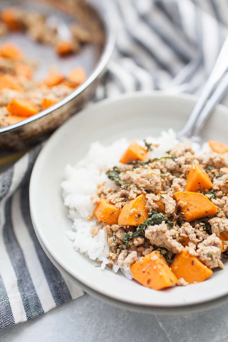 Wooden spoon scooping ground turkey and sweet potato mixture in a stainless steel skillet.
