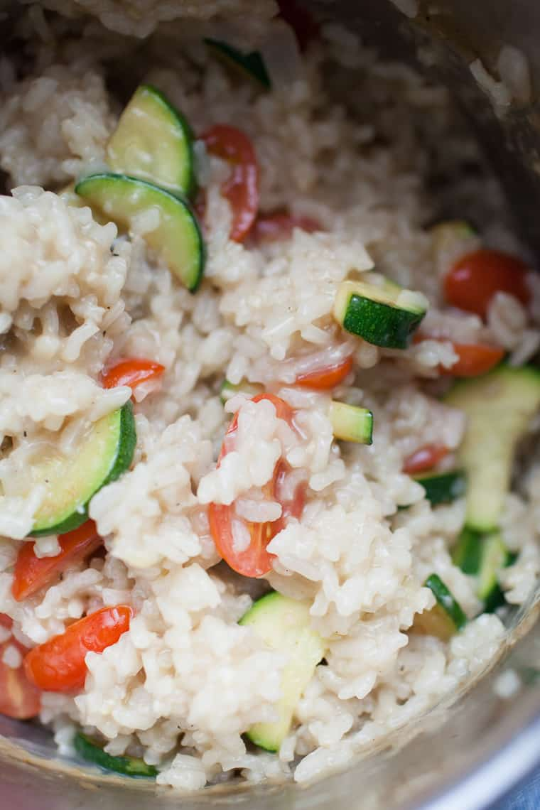 Stainless steel pot of creamy risotto with zucchini and tomatoes.