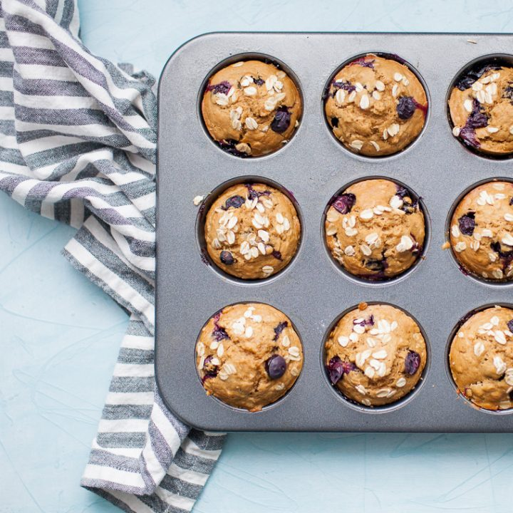 Golden blueberry muffins on a wooden bread board with blue and white linen.
