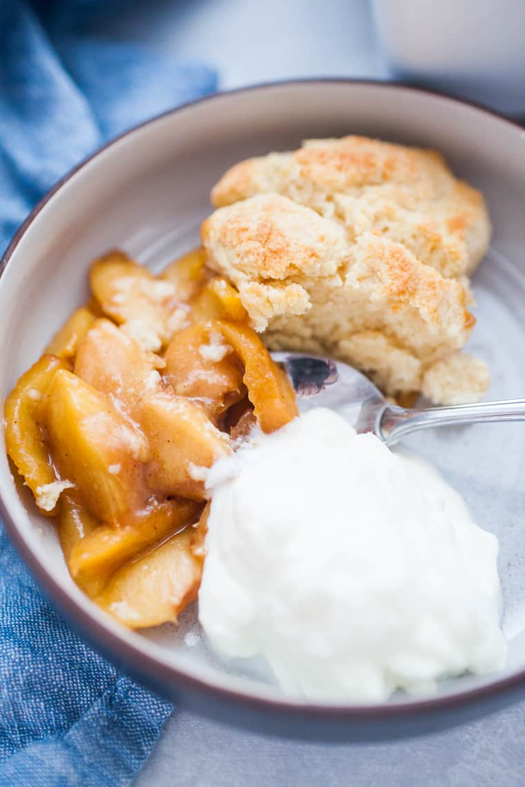 Bowl of peach cobbler with yogurt.
