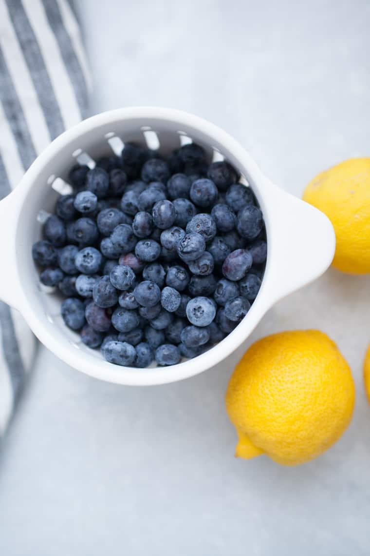 White colander of blueberries with lemons.