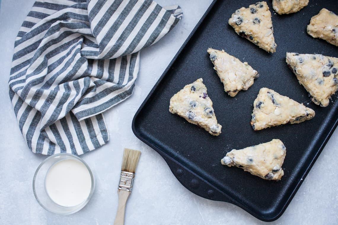Unbaked lemon scones on black baking pan, being brushed with cream.