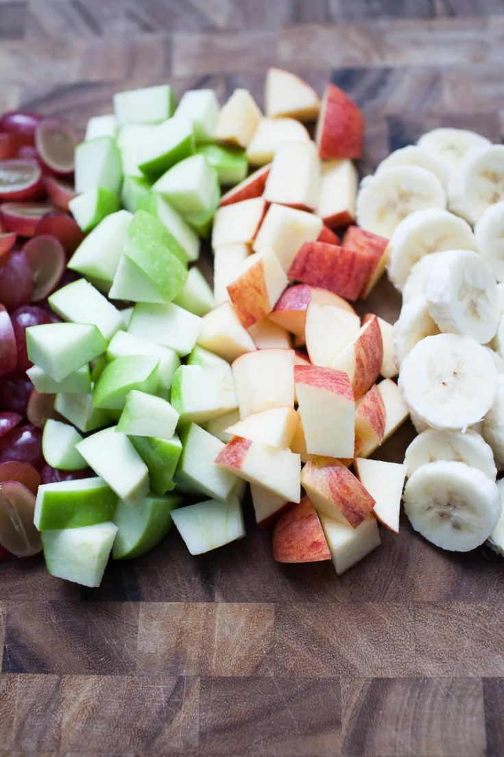 grapes, green apples, red apples and bananas on a wooden cutting board