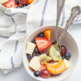simple fruit salad in two white cereal bowls on a blue and white striped kitchen towel