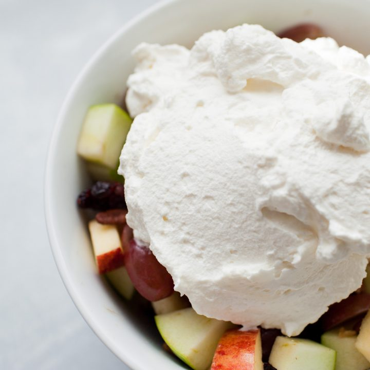 a bowl of fruit salad with a scoop of homemade whipped cream