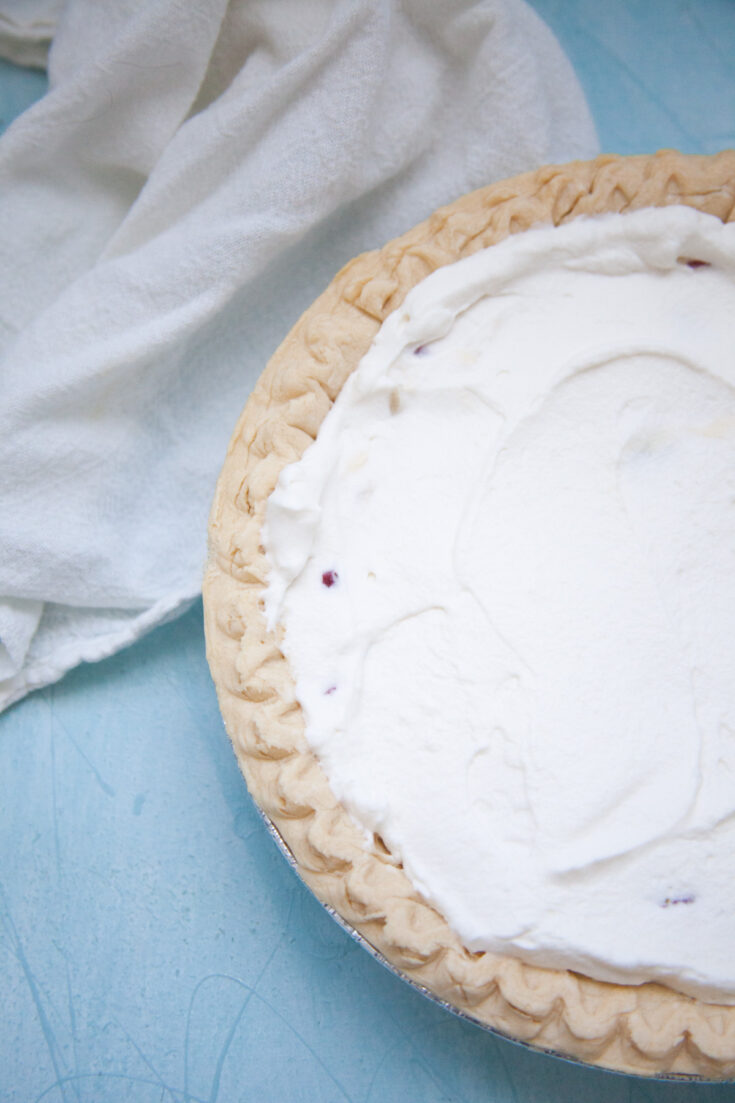 the almost finished pie with a layer of whipped cream on top