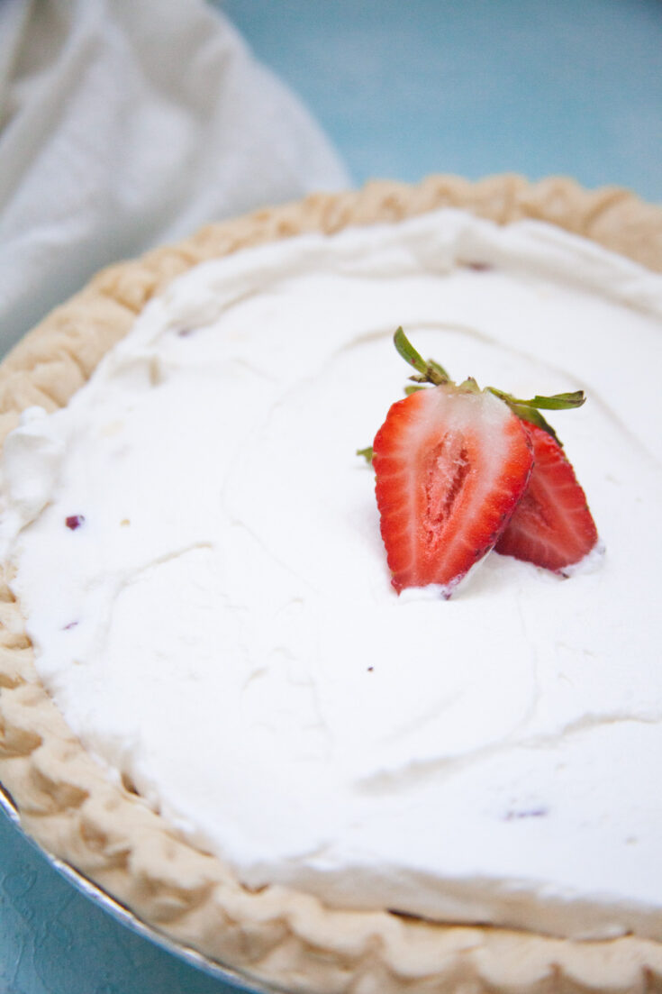 a closeup of a no-bake strawberry cream pie with sliced strawberries on top