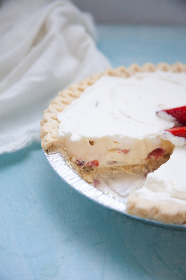 no bake strawberry cream pie in a silver dish with a slice cut out of the pie
