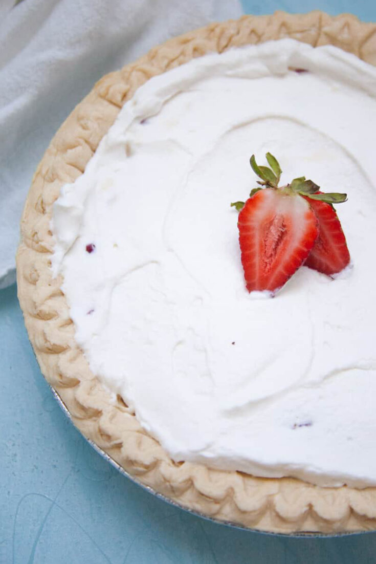 a completed no-bake strawberry cream pie on a blue background